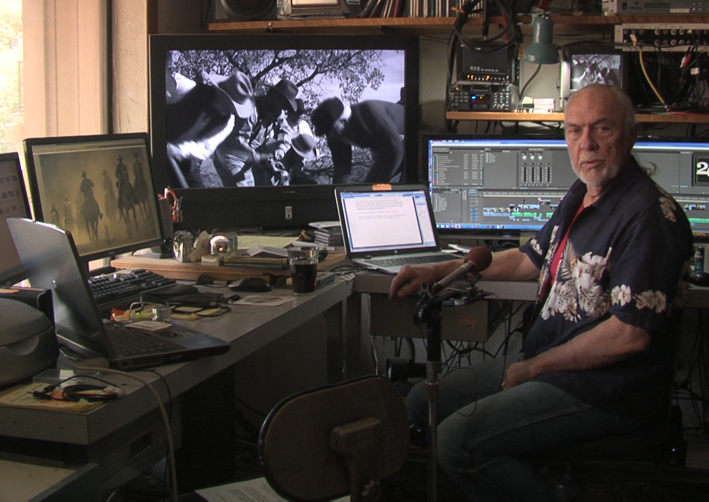 "Chuck Barbee in his editing suite. A scene from his documentary project , ""Wild West Country is on the large screen."